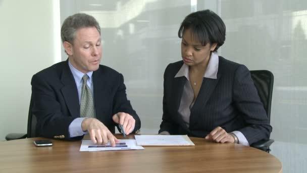 zwei Mitarbeiter diskutieren eine Arbeitspräsentation