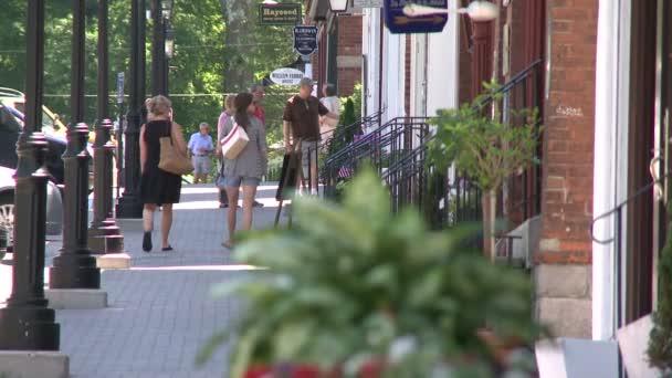 People walking down streetlight lined sidewalk