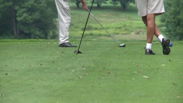 Golfista hity golfový míček, zatímco přítel vypadá