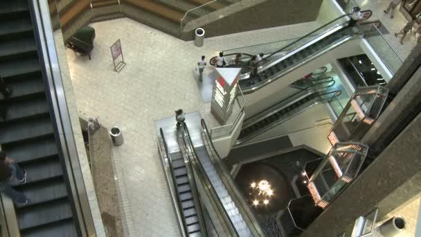 nakupující v obchoďáku u eskalátorů a výtahů