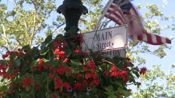 Červené květy, visící na znamení pro Main Street