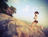 corridore della donna sul picco di montagna