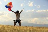 Žena s barevnými balónky