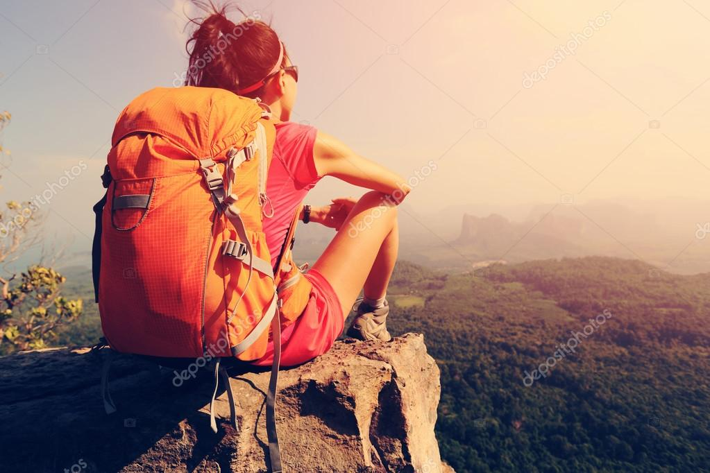 backpacker sitting on mountain peak