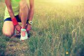 Fotografie mladá žena běžec vázání tkaničky
