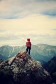 Photo backpacker hiking on mountain peak cliff