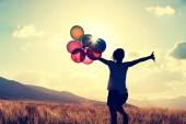 žena s barevnými balónky venku