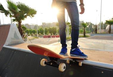 Skateboarding woman legs at sunrise skatepark