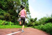 Fotografia atleta corridore in esecuzione su sentiero forestale.