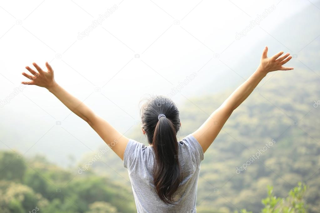 Woman open arms on mountain peak