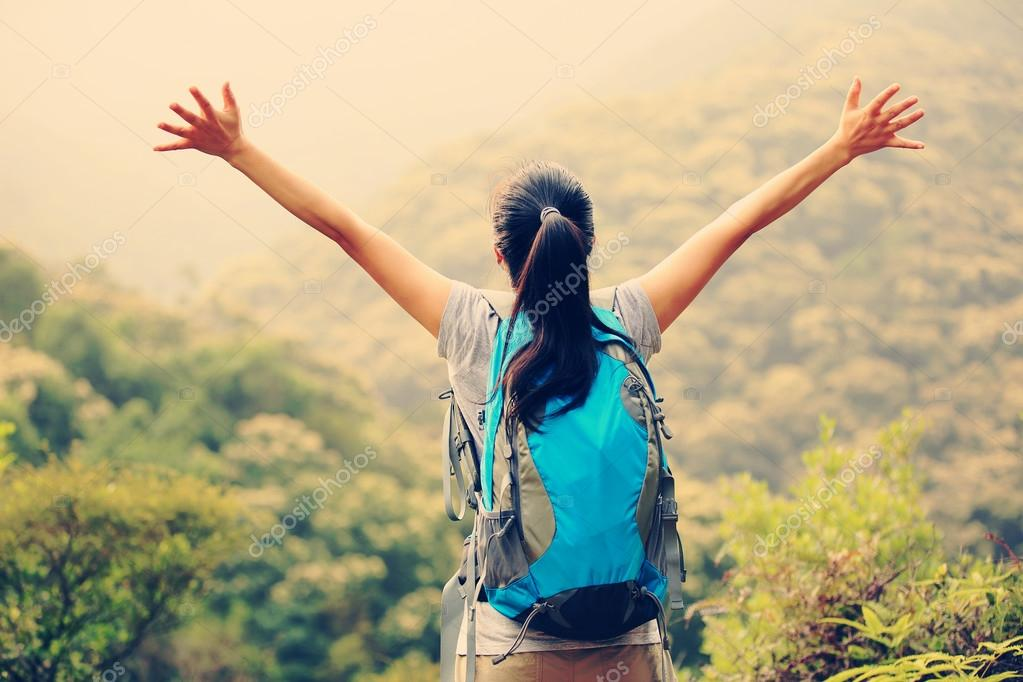 Woman open arms on mountain peak