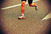 Gambe di atleti maratona correre sulla strada di città