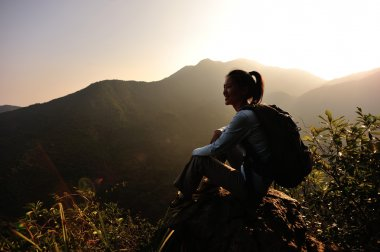 Woman hiker enjoy the view at mountain peak