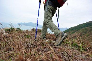 Woman hiker legs hiking on seaside trail