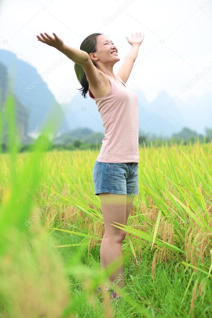 Young asian woman open arms at paddy field