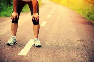 Tired female runner taking