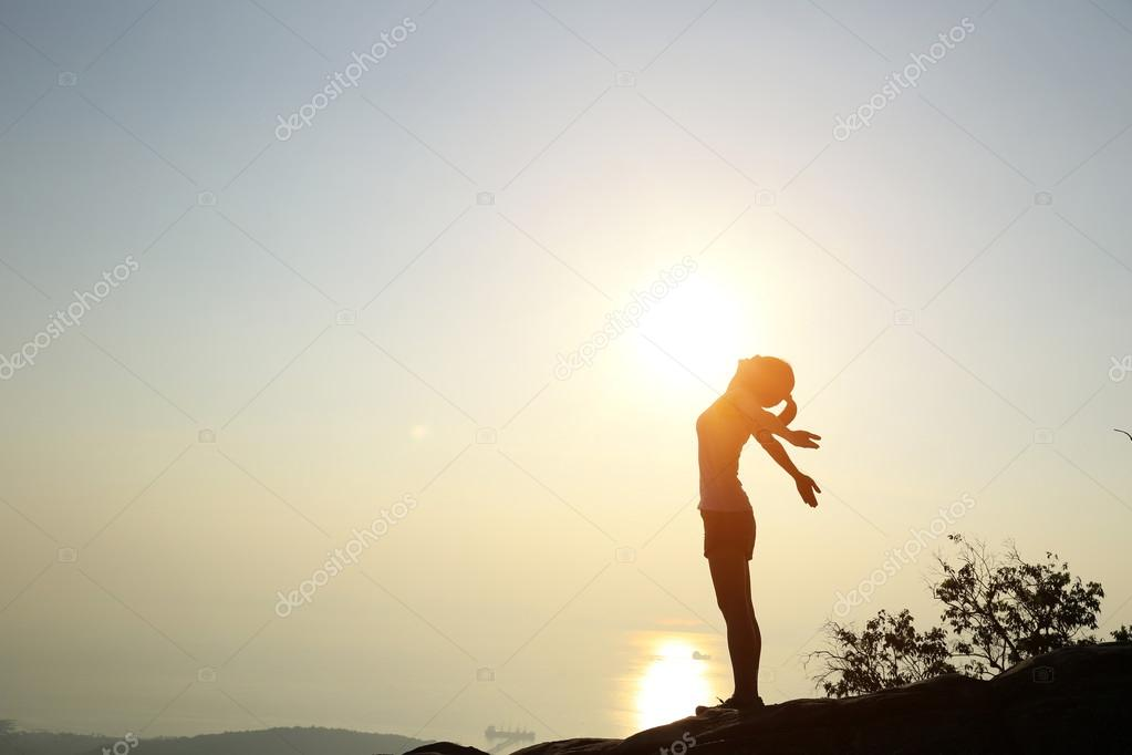 Woman with open arms at sunset