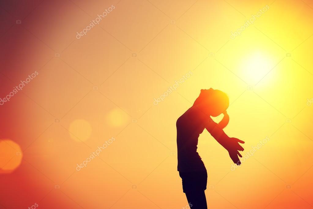 Female silhouette over sunset sky