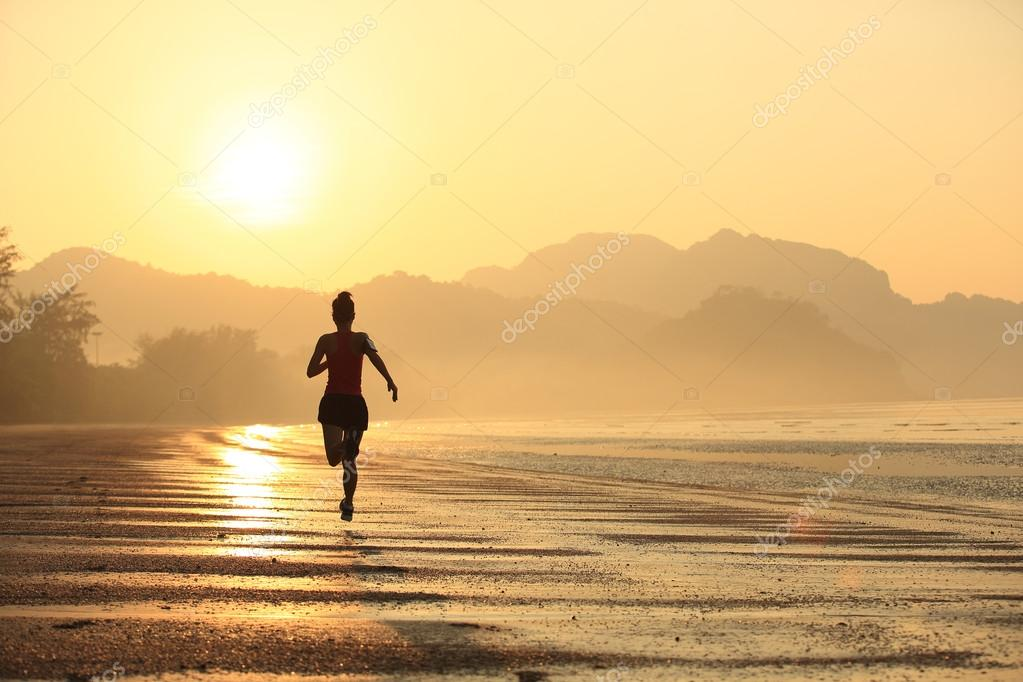 Asian woman running on beach