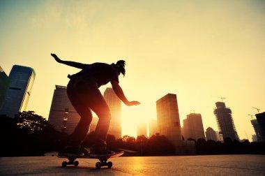 Skateboarder over sunrise city