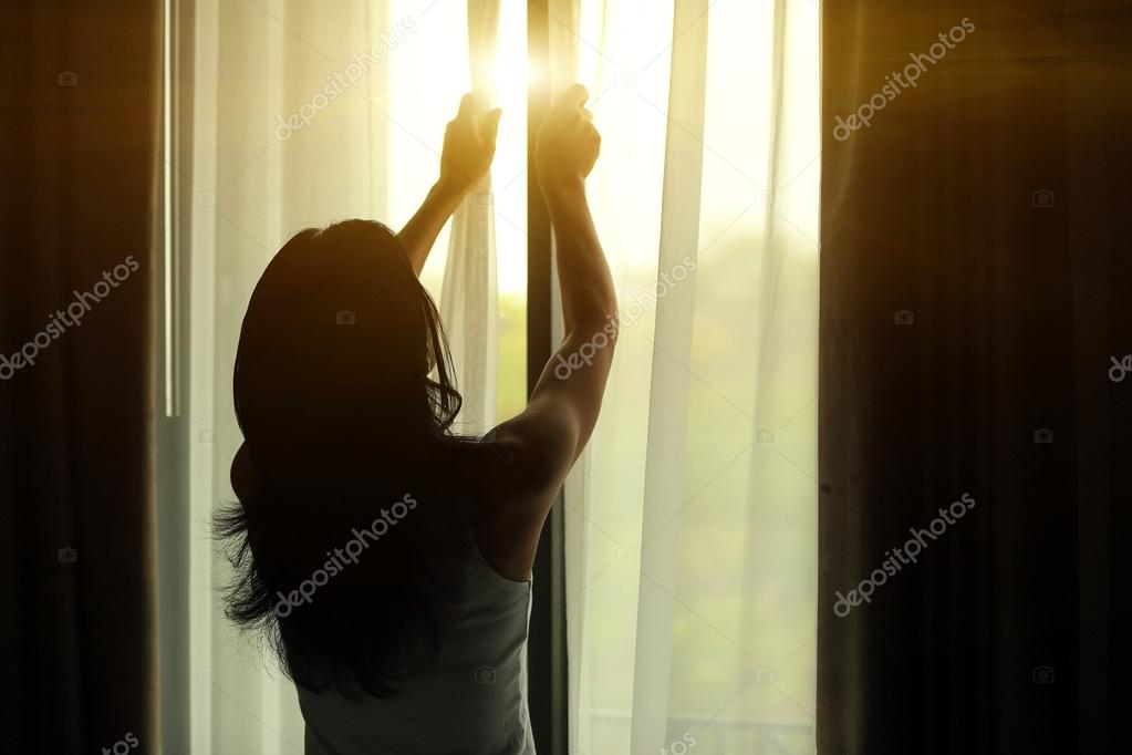 Young woman opening curtains in bedroom stock vector
