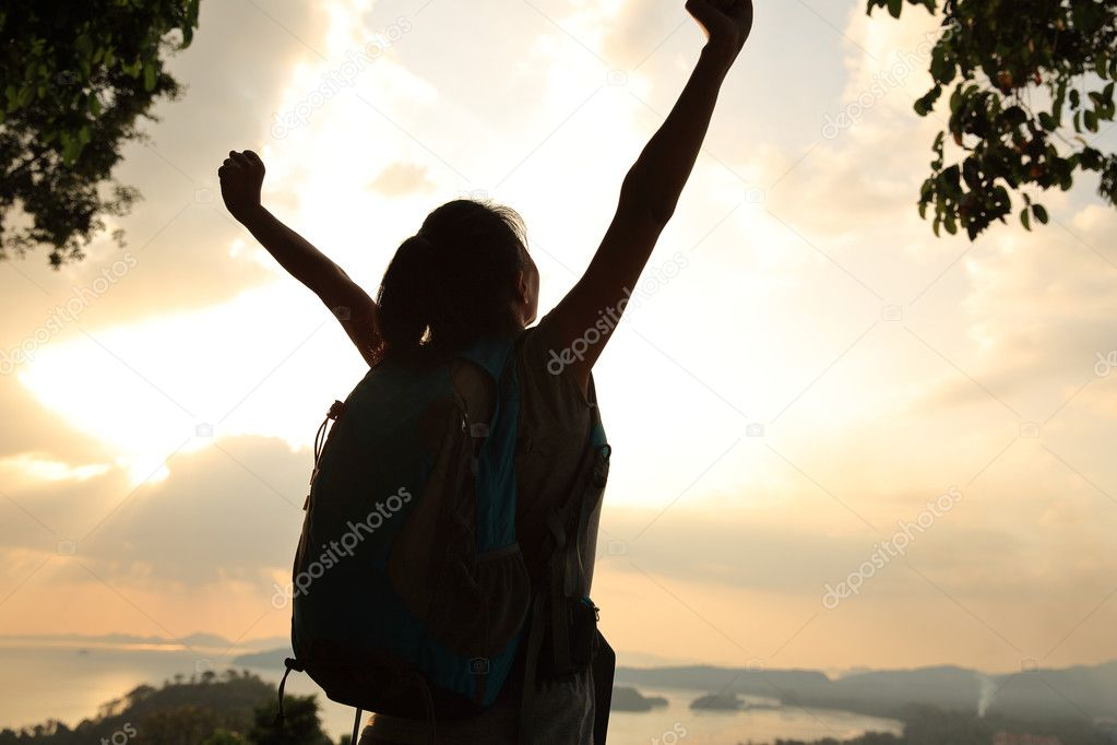 Cheering woman hiker on mountain top