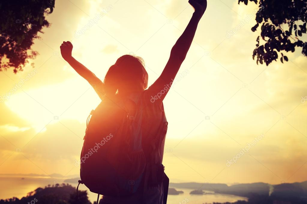 Cheering woman hiker on mountain top