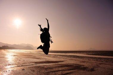 Cheering woman hiker jumping