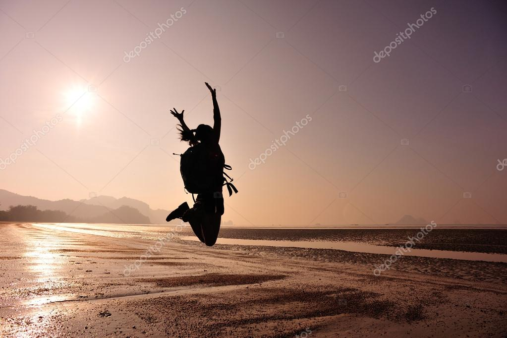 Cheering woman hiker jumping