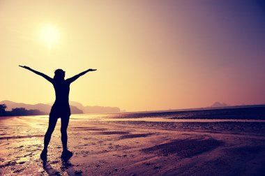 Cheering woman with open arms on beach