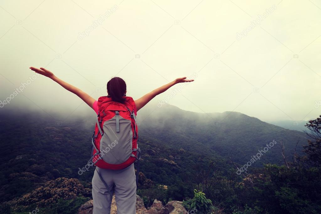 Cheering woman  at mountain peak