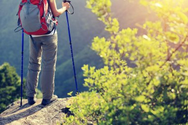 Woman hiker legs on mountain peak