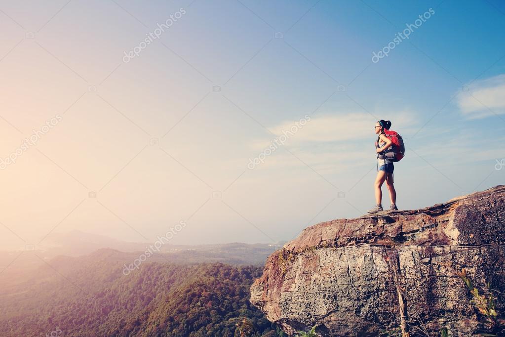 Woman hiker on mountain peak cliff