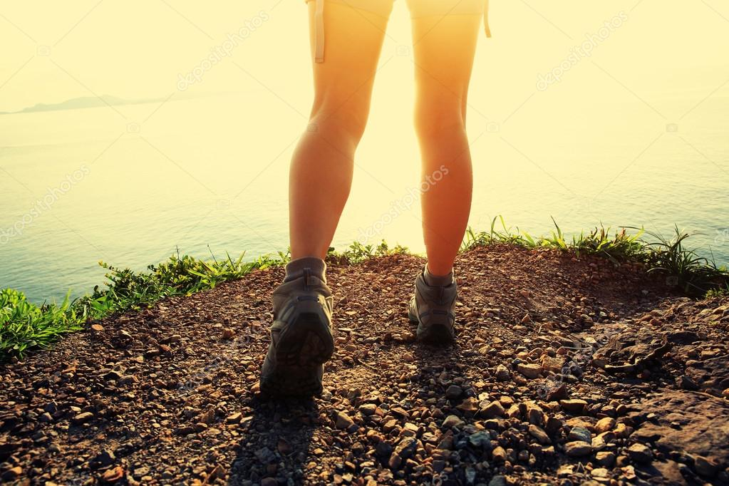 Woman hiker legs over seaside