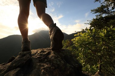 Woman hiker legs climbing on mountain