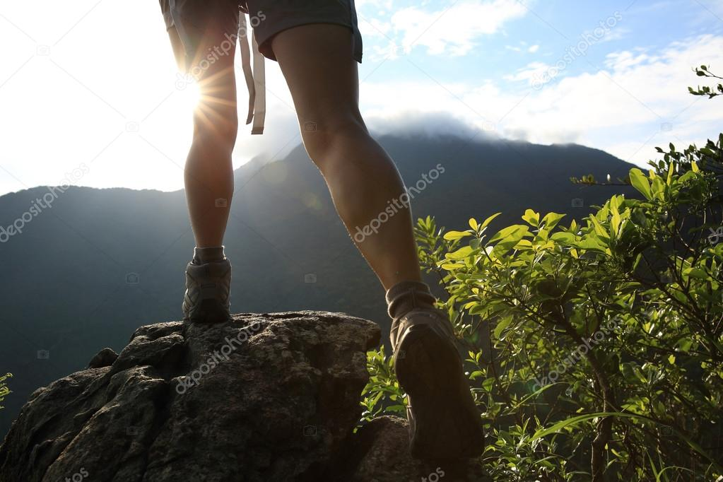 Woman hiker legs climbing on mountain