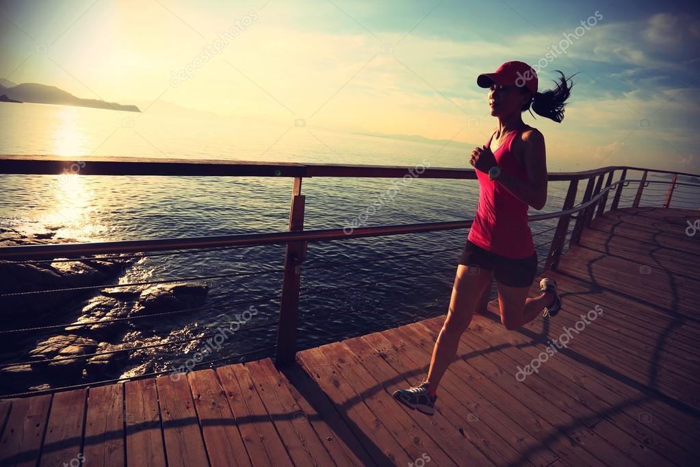 sporty female running on boardwalk