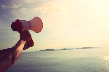Hand hold megaphone  under sunrise