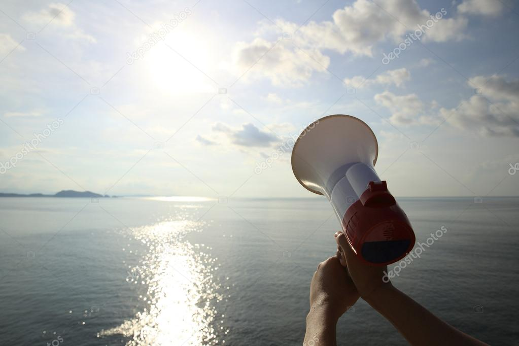 Hand hold megaphone with sea