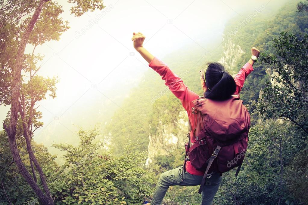 cheering female hiker with open arms
