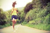 atleta femminile in esecuzione su sentiero nel bosco
