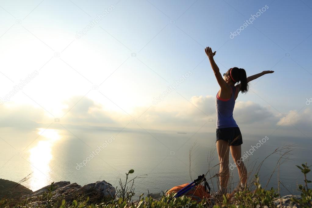 cheering  woman hiker on mountain peak