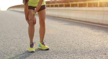 woman holding injured leg