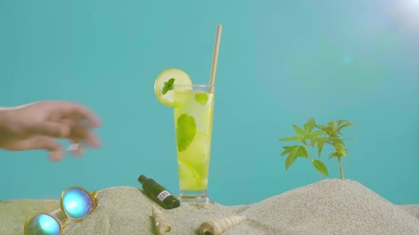 Hand aufheben erfrischende CBD-Limonade mit Eis neben Tropfenöl und einem Zweig Marihuana-Pflanze im Sand. Sonnenbrillen und Muscheln sind von der Seite zu sehen.