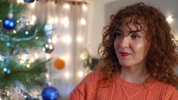 Lächelnde Brünette schmückt den Weihnachtsbaum im Wohnzimmer. Urlaubsvorbereitung.