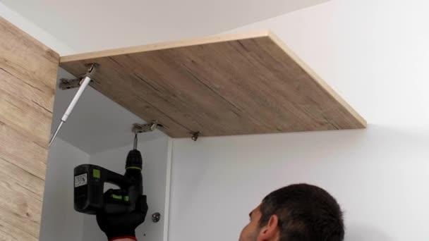 Tesař šroubuje a upevňuje závěsy na přední panel kuchyňských polic.