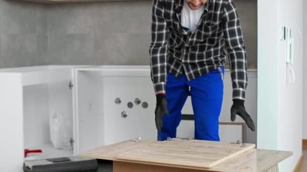 Der Tischler schraubt das Scharnier ein und montiert es an der Frontplatte der Küchenregale.