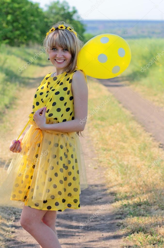 b5028d0fa4ee32 Яскрава, сонячна, грайливий, дівчинкою в жовтий Літнє плаття з горошок,  сміючись і тримає м'яч в жовтий горох. Цікаві фото, символізуючи літніх  достаток, ...