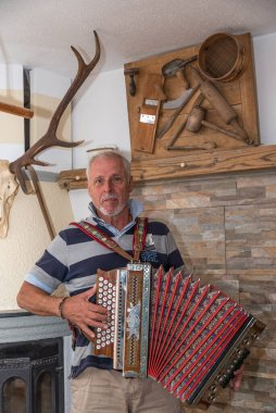 Man plays traditional old Styrian accordion in a farmhouse parlor