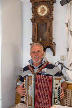 Musician plays with accordion in old farmhouse parlor